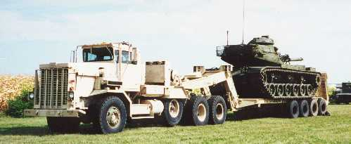 Truck towing a military tank